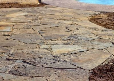 Detail shot of the stones that make up the new outdoor patio installation that reaches to the below ground swimming pool.