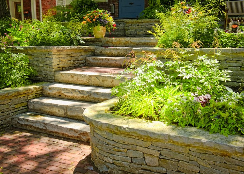 Natural stone landscaping in home garden with stairs and retaining walls. These are the sort of hardscapes a clean cut lawn care will install.