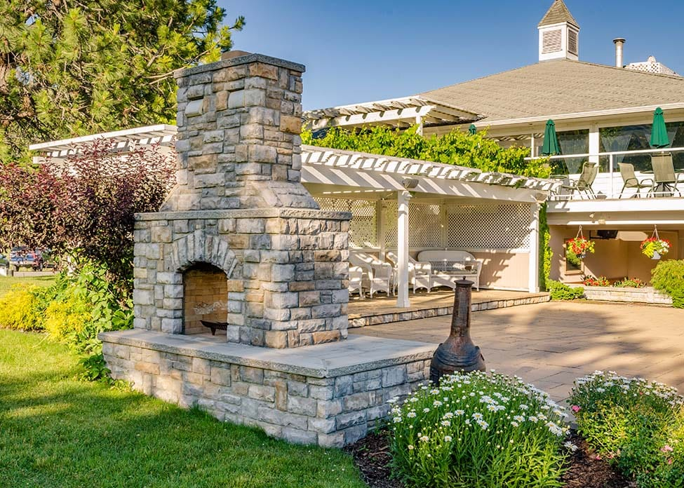 Large Stone fire pit with large backyard patio, surrounded by flowery landscaping.These are the sort of outdoor living hardscapes A Clean Cut Lawn Care can design & install.
