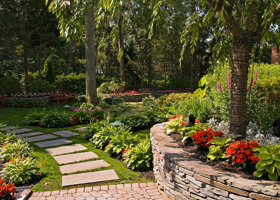 Backyard Landscaping with retaining wall and path / walkway with Flowers in Bloom. These are the sort of hardscapes A Clean Cut Lawn Care can design & install.