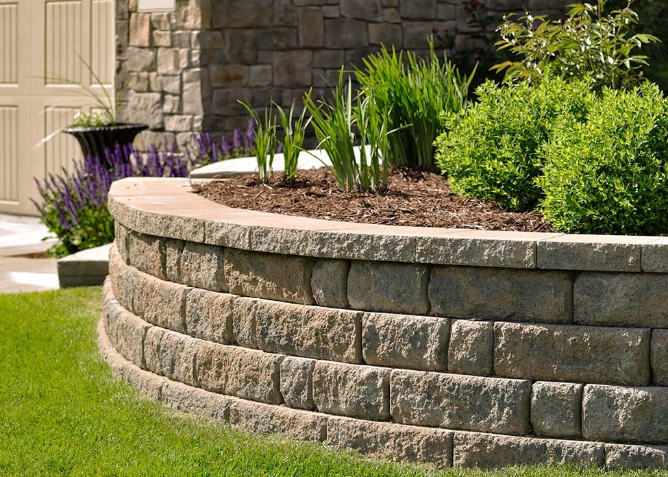 Natural stone landscaping in home garden with retaining walls and shrubs. These are the sort of hardscapes A Clean Cut Lawn Care can design & install.
