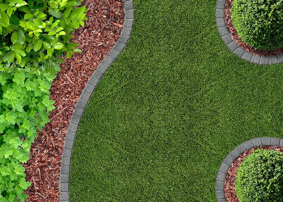 A view from above of grass separated by paving stones from the mulch areas and shrubs.