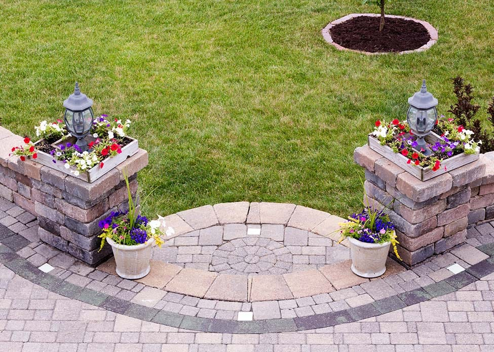 Curved entrance to an outdoors patio with shallow steps leading to a brick paved living area flanked by two pillars with lamps and colorful flowers in square pots, high angle view with green grass. These are the sort of hardscapes A Clean Cut Lawn Care can design & install.