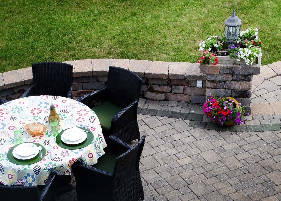 View looking down at a brick paved outdoor living area on an open-air patio with a dining table and chairs overlooking green lawns with outdoor lighting