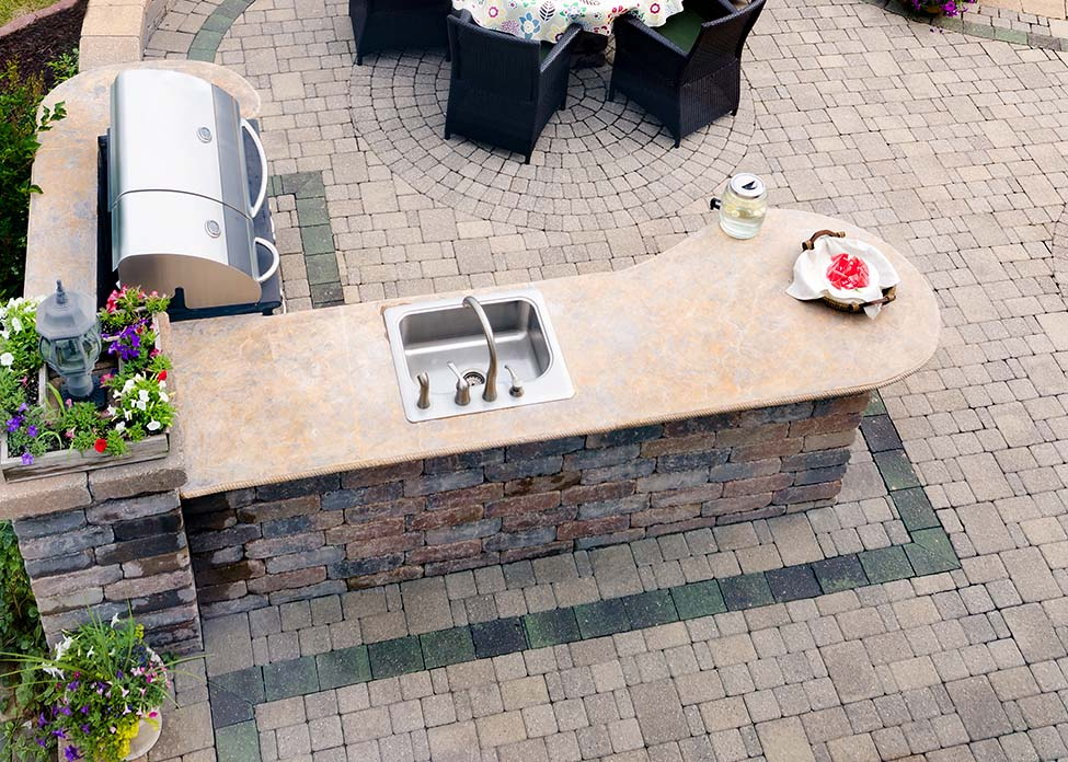 View looking down at a brick paved outdoor living area on an open-air patio with a gas BBQ and concrete kitchen counter alongside a dining table and chairs overlooking green lawns. These are the sort of Outdoor Living hardscapes A Clean Cut Lawn Care can design & install.