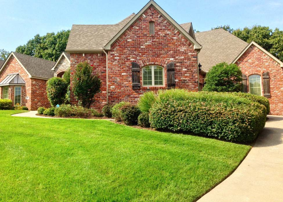 A red brick home on a sunny day with freshly cut grass and many trimmed shrubs. This is the sort of landscape designed, installed, and maintained / serviced weekly by A Clean Cut Lawn Care
