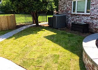 A picture of a side yard with freshly laid green sod grass next to a retaining wall, illustrating the type of lawn care work by A Clean Cut Lawn Care