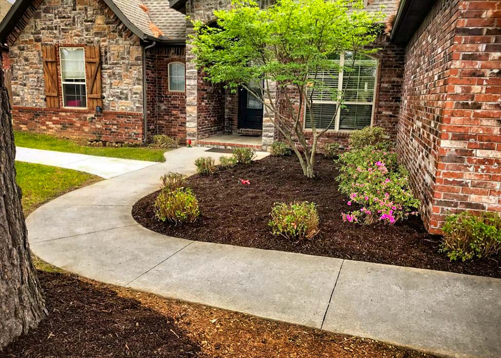 A Stone house on a sunny day with freshly installed mulch, shrubs, and green grass.