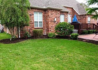 A picture of a brick house with a manicured green yard and trimmed shrubs, illustrating the type of lawn care work by A Clean Cut Lawn Care