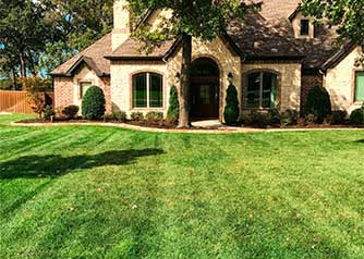 A picture of a large house with an immense green yard and trimmed shrubs, illustrating the type of lawn care work by A Clean Cut Lawn Care