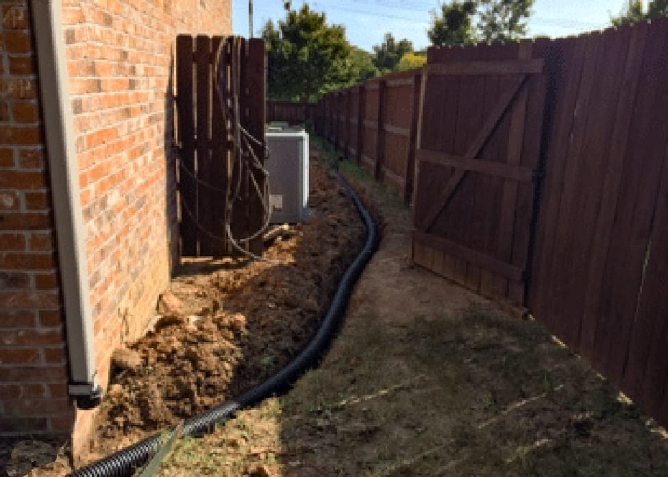 A large flexible black pipe being buried in a trench next to a house, one of the steps of installing french drains