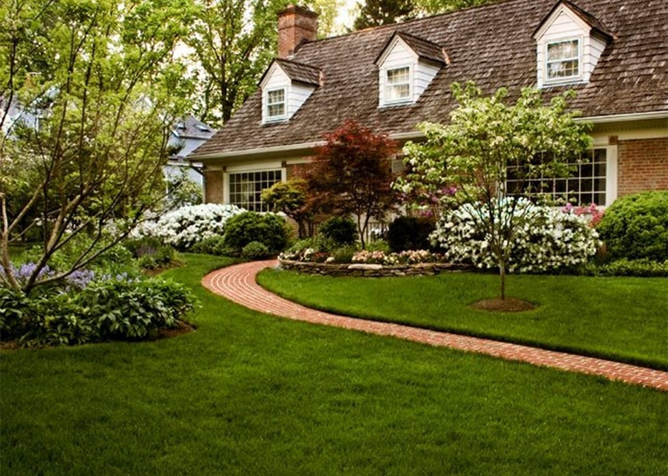 A large house fronted by a large lawn with green grass and landscaped plants, showing the value of aeration, overseeding, fertilization, weed barriers, soil testing, and organic soil rebuilding.